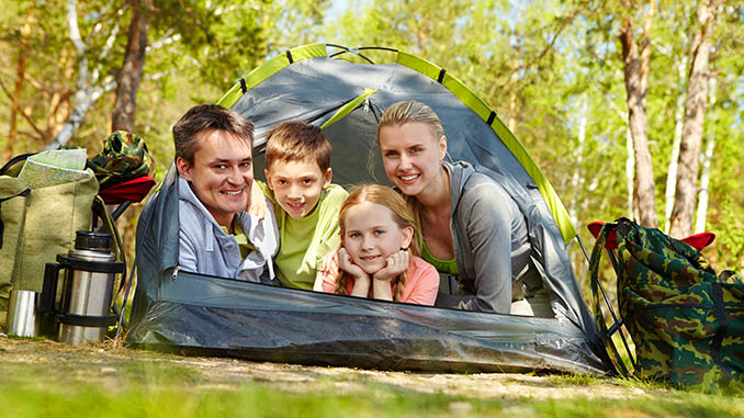 family of four camping in the forest