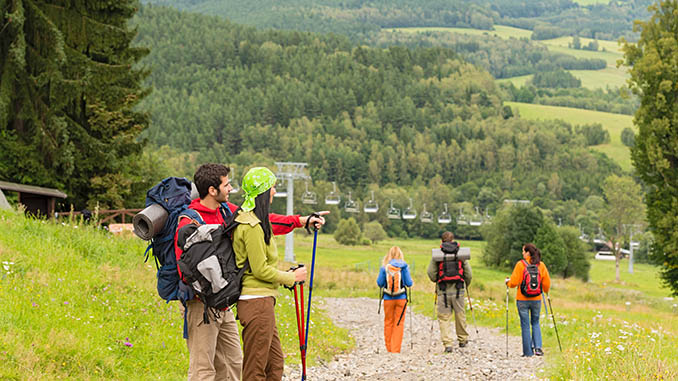 Young hikers with backpacks enjoying scenic view on the mountain