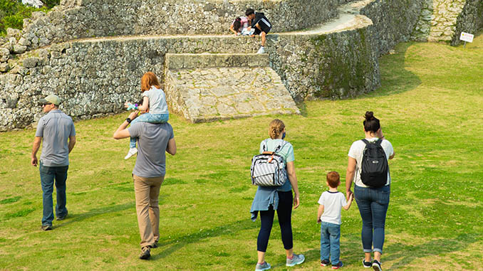 people walking near stone structure