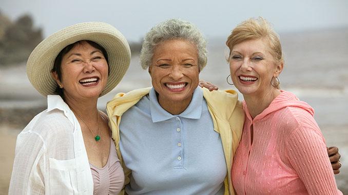 senior women embracing at beach