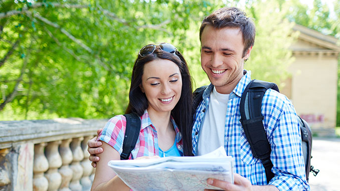 smiling couple travelers holding a map