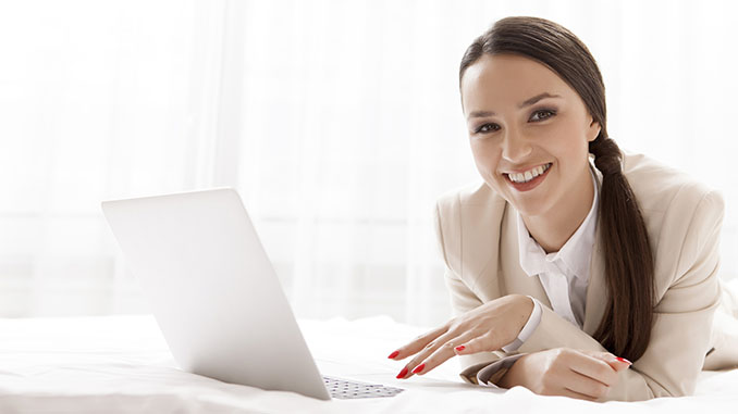smiling woman with laptop in bed