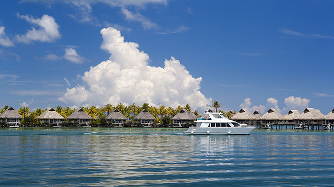 White boat traveling past thatched huts