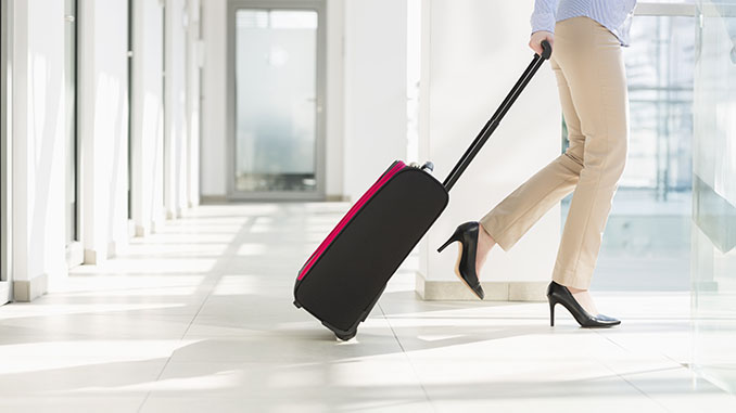 woman with luggage exiting airport