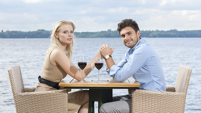 young couple holding hands at outdoor restaurant by lake